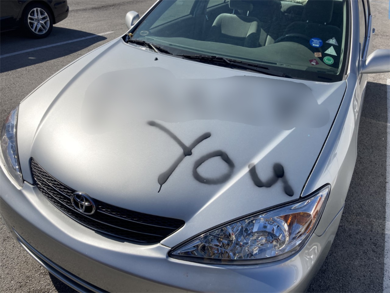 """F--- you"" is written across the hood of a car."